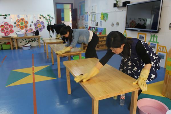保育老师动作规范、熟练的进行桌面消毒。